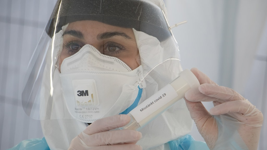 Kvinna i skyddsutrusning håller i covidprov.  Foto Jan Alfredsson
