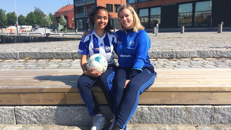 Patricia Palar och tränaren Jessica Holmström sitter på en träbänk med en fotboll i famnen.