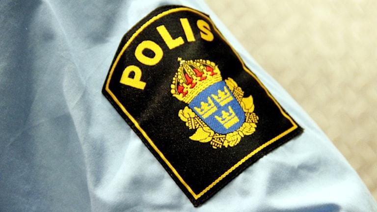 En skjortärm med polismärket på.