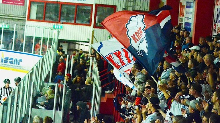 En hockeyläktare med vajjande flaggor. Det är KRIFs klack som hejar.