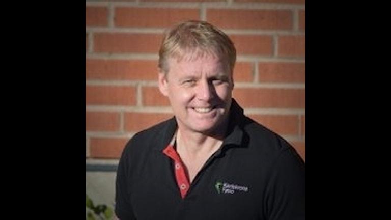 En porträttbild på en glad Anders Broström framför en tegelvägg.