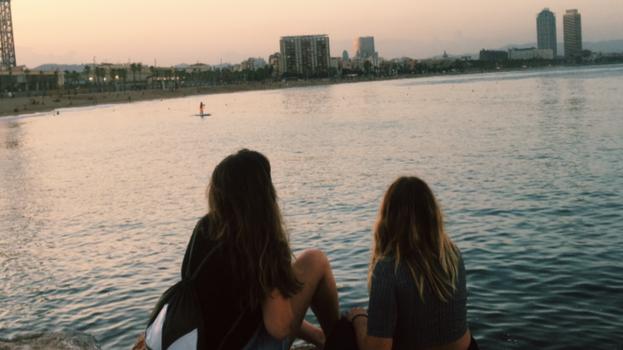två kvinnor med ryggen vända mot kameran i solnedgång.