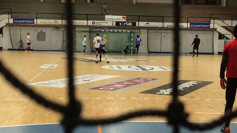 En inomhusplan där högstadieelever spelar fotboll.