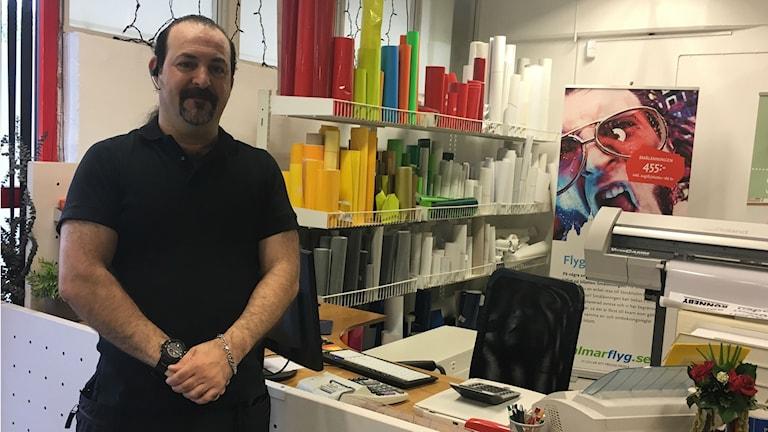 Wasim Khalil står vid materialen han ska använda till sin trycksaksfirma.