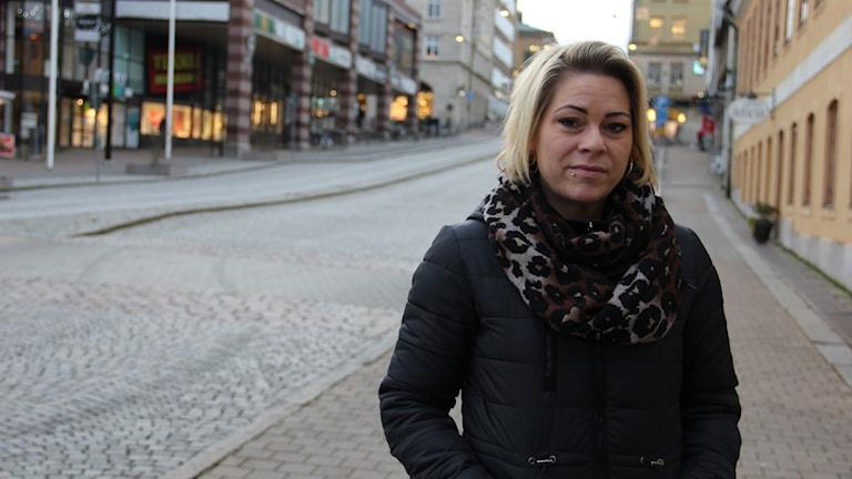 Petra i svart jacka och leopardfärgad sjal. Hon ser in i kameran och står vid en kullerstensgata.