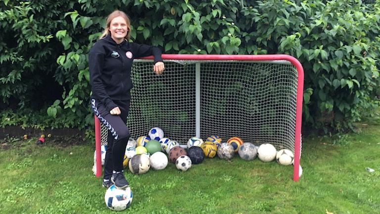 Maja Bodin står framför ett fotbollsmål med en fotboll under foten.