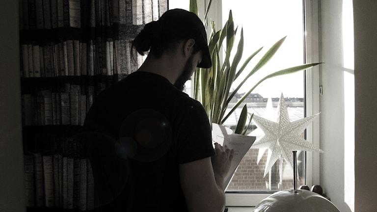 Svartvit bild av man läsande papper vid ett fönster.