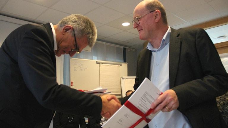 Peter Örn bockar efter att han lämnat över en rapport till landstingsrådet Kalle Sandström.