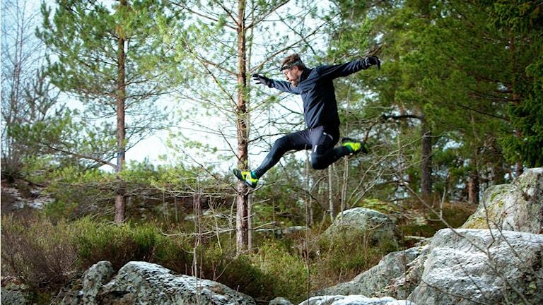 Daniel Karlsson hoppar fram över stenar med skog i bakgrunden.