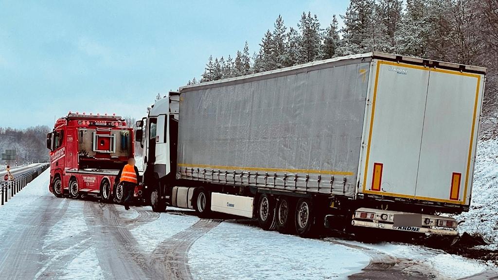 En lastbil får hjälp av en bärgare att ta sig upp ur diket.
