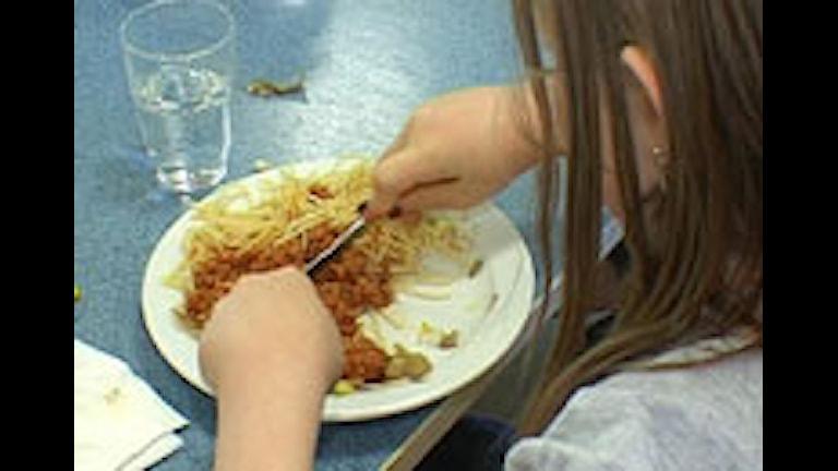 En flicka äter spagetti och köttfärssås.