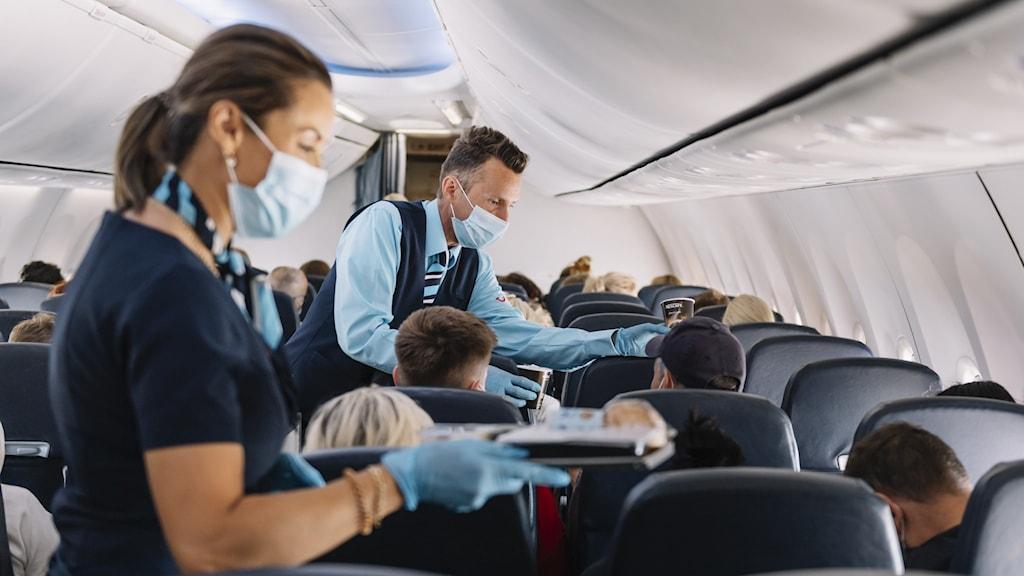 Flygpersonal som använder munskydd.