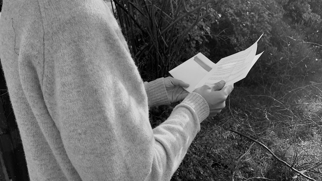 En mansperson sedd snett bakifrån hållandes ett vitt brev.