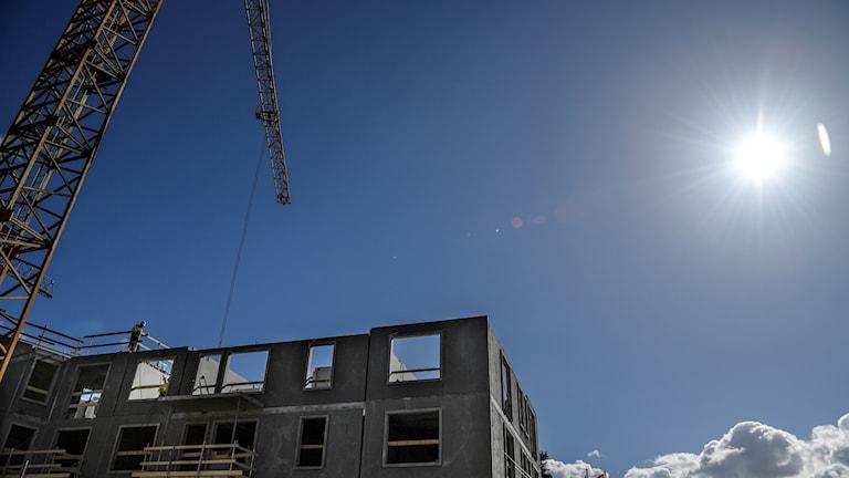 Byggnad uppförs med kran.