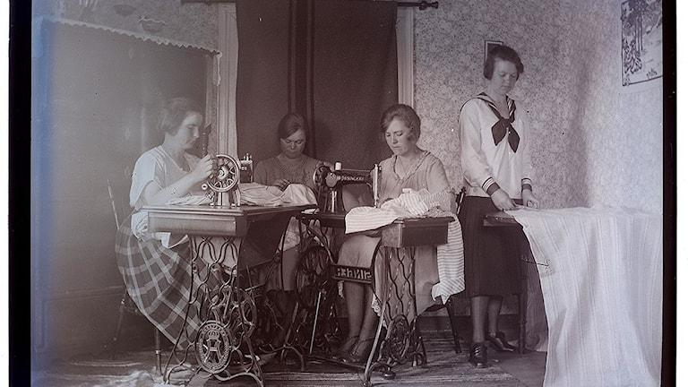 Ett gammalt fotografi av kvinnor vid symaskiner.