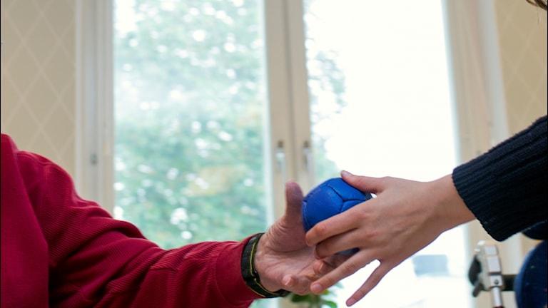 En hand som sträcker över en blå boll till en äldre hand.