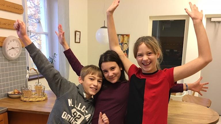 Tre glada femteklassare står bredvid varandra och sträcker upp händerna i luften.