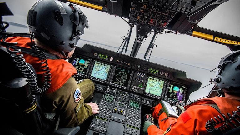 Två helikopterpiloter vid manöverpanelen i en helikopter 14.