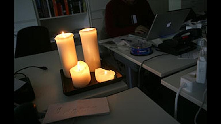 Fyra stearinljus lyser upp ett skrivbord med en dator. Foto: Fredrik Sandberg/Scanpix.