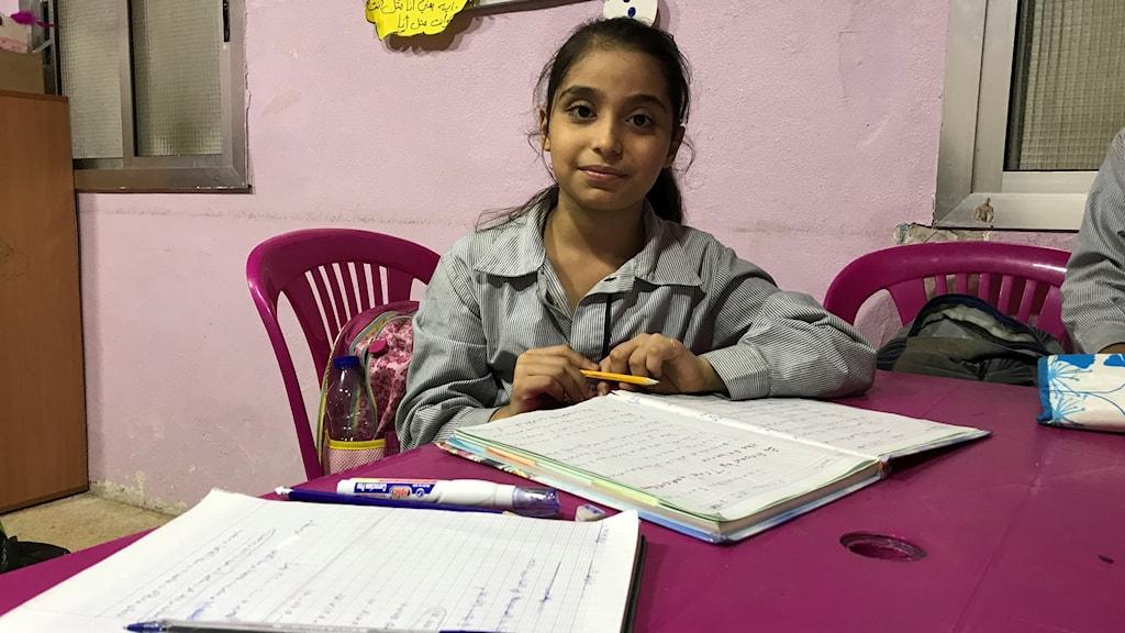 En flicka som sitter och pluggar vid ett bord.