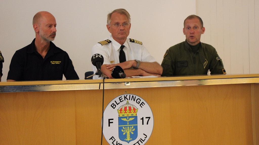 Tre män på rad under en presskonferens