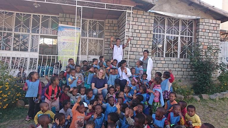 Dagisbarn i Etiopien sitter på trappan till förskolan. Carl Andreasson sitter i mitten.