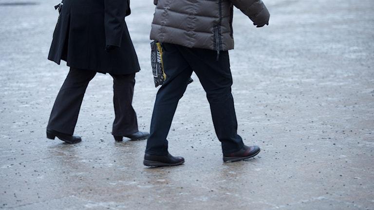 Två personer går på isig gata