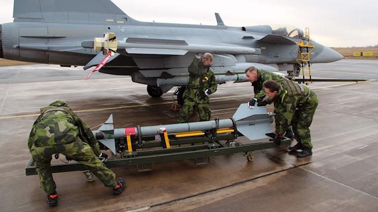 Soldater med en jaktrobot som ska fästas under ett Jas-Gripen.