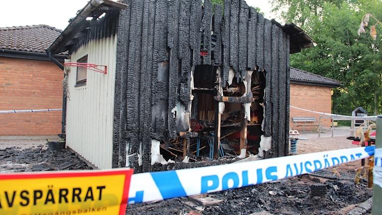 Förrådsbyggnad med svart, brandskadad gavel. Polisens avspärrningstejp framför.