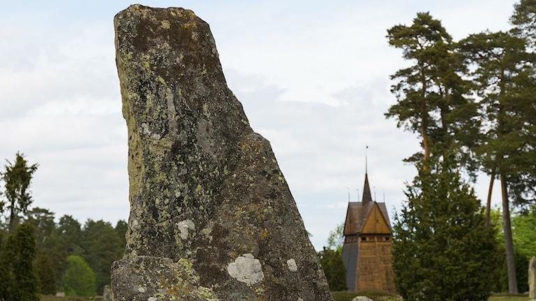 En hög sten i förgrunden och en kyrka i bakgrunden vid Hjortsberga gravfält.