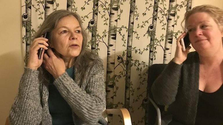 Två kvinnor sitter i var sin fåtölj och pratar i telefon.