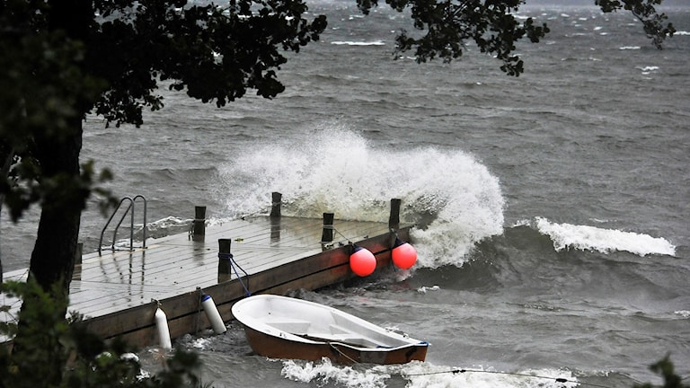 Vind piskar upp vågor som slår över en brygga där det ligger en vattenfylld eka.