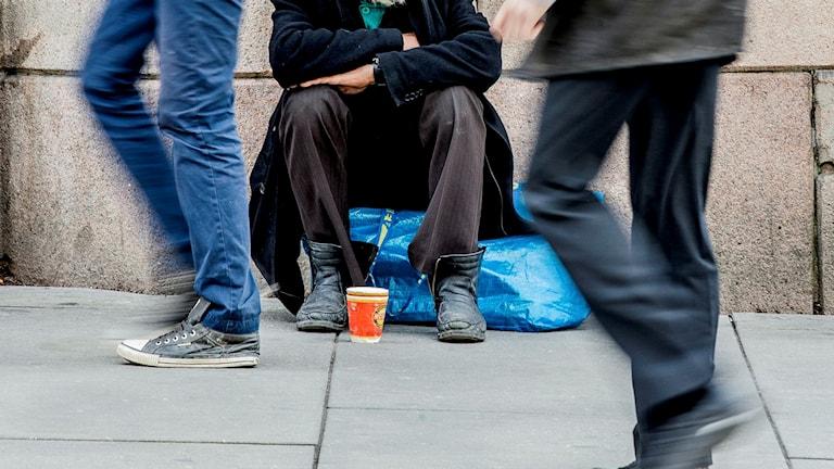En eu-migrant sitter och tigger och människor går förbi.