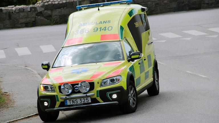 En gul ambulans på vägen.
