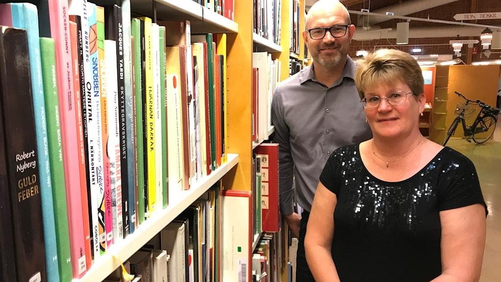 En man och en kvinna vid en bokhylla i ett bibliotek