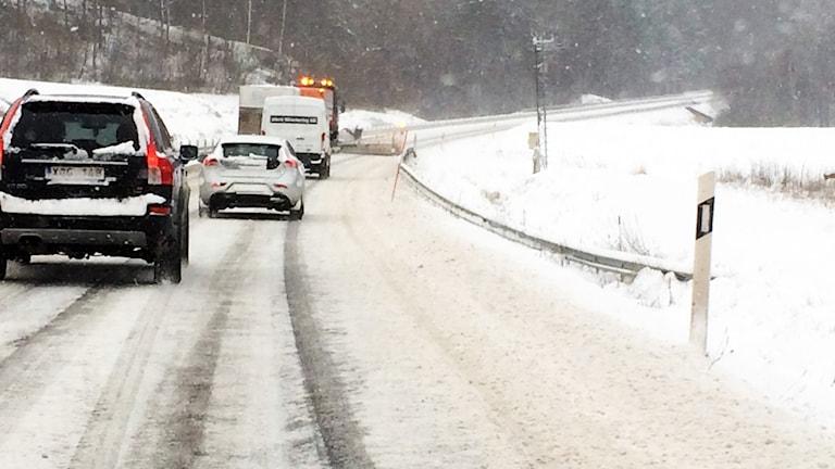 En kö av bilar bakom en plogbil på en snöig väg