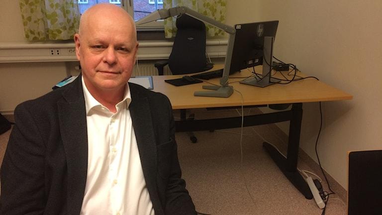 Gelander sitter bakom sitt skrivbord  på sitt kontor.