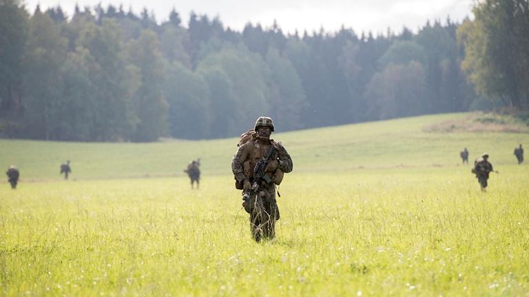 Kamoflerada militärer går på ett fält