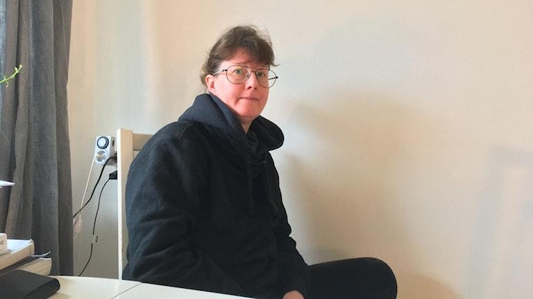 Cilla i glasögon på stol framför vit vägg.