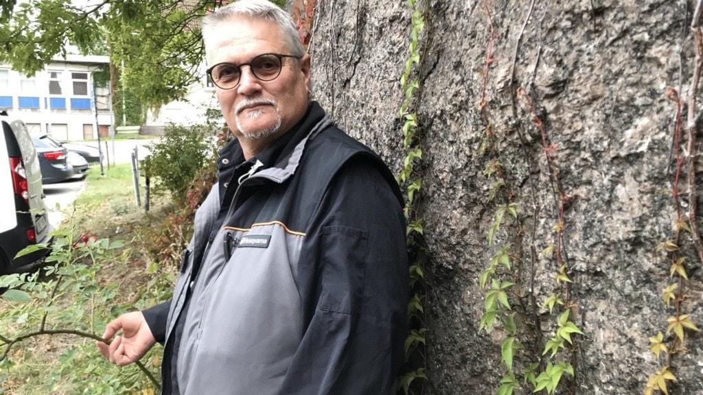 En äldre man står vid ett träd.