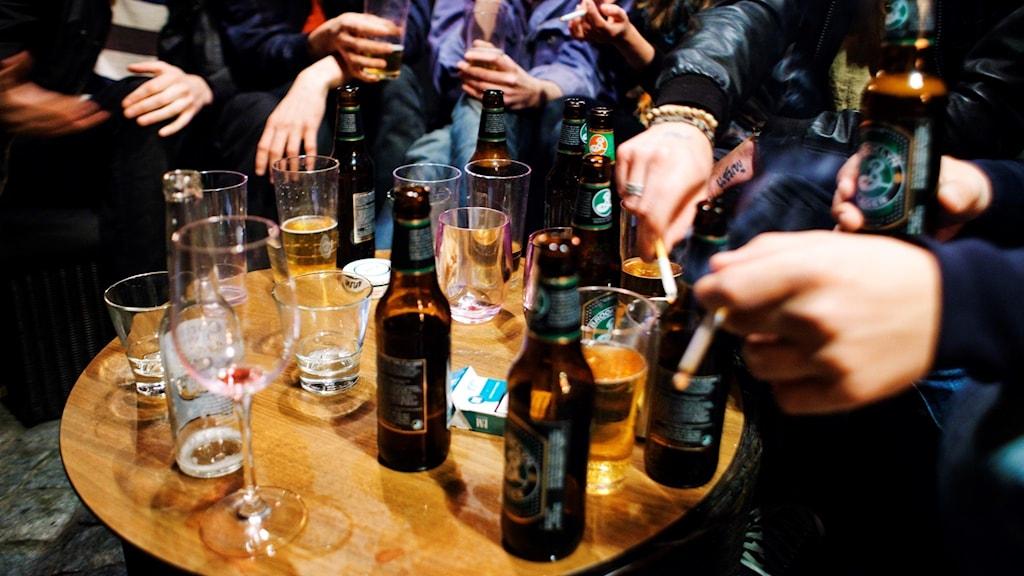 Flera ölflaskor på ett bord och människor runt som dricker.