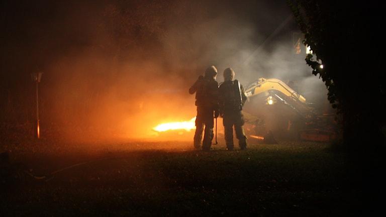 Två ur räddningstjänsten står framför branden. Grävskopan syns vid huset.