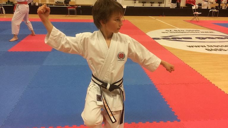 Pojke i vit karatedräkt sträcker ut armarna