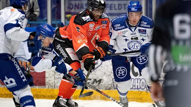 Spelare från KHK och Leksand kämpar om pucken.