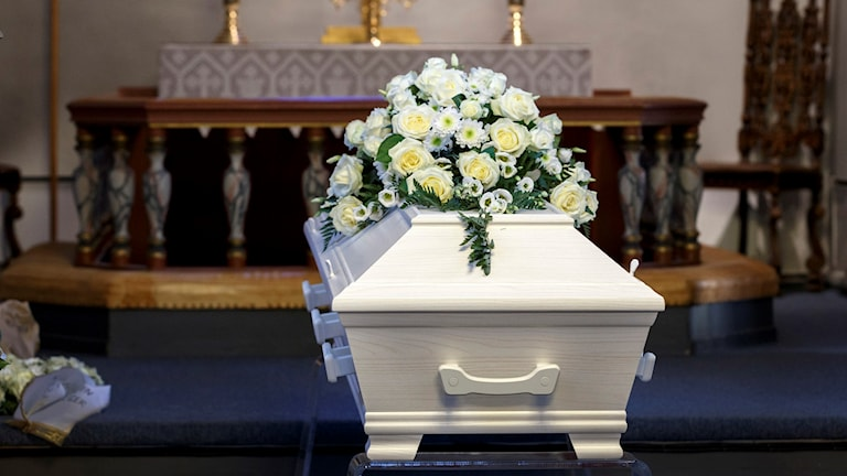 En vit kista med blommor på.