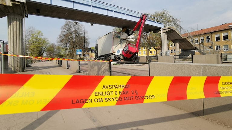 En lastbil med kran har kört in gångbron över E22 i Jämjö och det är risk för att gångbron ska rasa.
