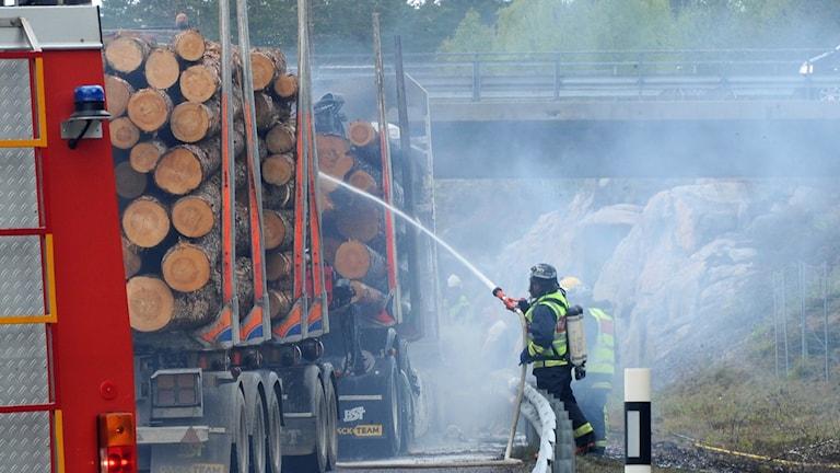 Brand i en timmerbil, brandman sprutar vatten.