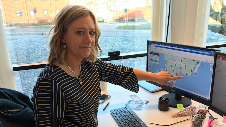 Jessica Holmström i Karlshamn är marknadsansvarig för SMS-livräddare. Hon sitter vid sitt skrivbord och pekar på en skärm som visar var och hur många livräddare det finns i landet.
