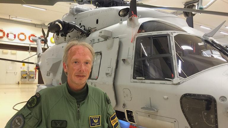 Piloten Göran Svedjer vid en gråmålad helikopter 14