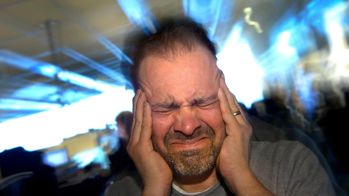 En man som håller för öronen och grimaserar.